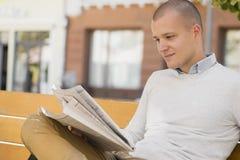 Homem novo que senta-se no banco e que lê jornais fotos de stock royalty free
