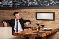 Homem novo que senta-se no café que espera alguém fotografia de stock royalty free
