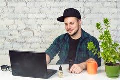 Homem novo que senta-se no escritório com uma xícara de café e que vaping Imagem de Stock