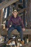 Homem novo que senta-se no feixe de madeira Imagem de Stock Royalty Free