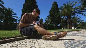 Homem novo que senta-se no gramado, escrevendo no caderno, estudante que faz anotações, educação filme