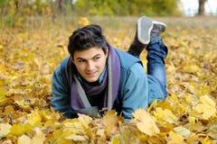 Homem novo que senta-se no parque. Imagens de Stock