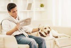 Homem novo que senta-se no sofá branco com cão em casa imagem de stock