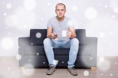 Homem novo que senta-se no sofá com o copo do chá e da tevê de observação no hom Foto de Stock