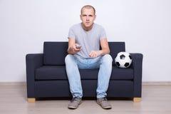 Homem novo que senta-se no sofá e no futebol de observação na tevê em casa Foto de Stock