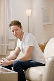 Homem novo que senta-se no sofá em casa Foto de Stock
