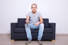 Homem novo que senta-se no sofá e na tevê de observação em casa Foto de Stock Royalty Free