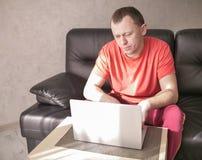 Homem novo que senta-se perto de um portátil em sua sala de visitas em uma tarde ensolarada, copyspace fotos de stock royalty free