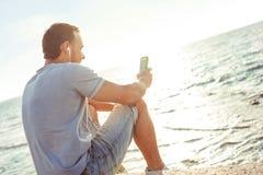 Homem novo que senta-se perto do mar com telefone celular fotos de stock