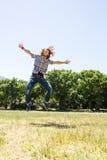 Homem novo que sente livre no parque Fotografia de Stock Royalty Free
