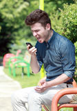Homem novo que shouting no telefone Foto de Stock Royalty Free