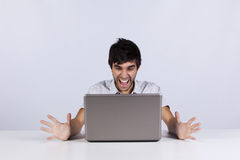 Homem novo que shouting a um portátil Fotos de Stock