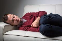 Homem novo que sofre da dor severa da barriga Imagens de Stock Royalty Free