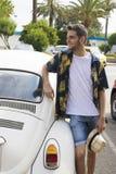 Homem novo que sorri com carro do vintage foto de stock