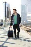 Homem novo que sorri com a mala de viagem na plataforma do estação de caminhos-de-ferro Imagens de Stock Royalty Free
