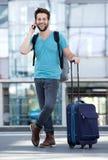 Homem novo que sorri com a mala de viagem no aeroporto Fotografia de Stock