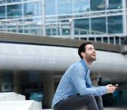 Homem novo que sorri com telefone celular Imagens de Stock Royalty Free