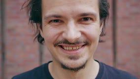 Homem novo que sorri contra um fundo da parede de tijolo vídeos de arquivo