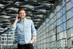 Homem novo que sorri dentro da construção com telefone celular Fotografia de Stock