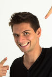 Homem novo que sorri e que aponta nsi mesmo fotografia de stock