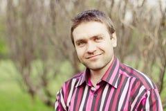 Homem novo que sorri e que olha a câmera ao ar livre Foto de Stock