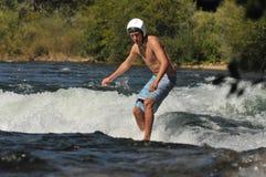 Homem novo que surfa uma onda do rio com capacete Foto de Stock
