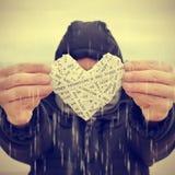 Homem novo que swhoing um coração sob a chuva, com um efeito do filtro Fotografia de Stock Royalty Free