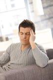 Homem novo que tem a dor de cabeça Foto de Stock