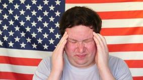 Homem novo que tem a dor de cabeça no fundo de uma bandeira dos EUA vídeos de arquivo