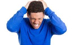 Homem novo que tem a dor de cabeça realmente má, colocando ambas as mãos na parte traseira de cabeça Foto de Stock
