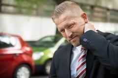 Homem novo que tem a dor de pescoço Fotografia de Stock Royalty Free