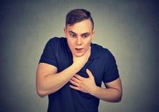 Homem novo que tem o ataque de asma ou que bloqueia o sofrimento dos problemas da respiração fotografia de stock