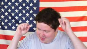 Homem novo que tem o divertimento e que dança no fundo de uma bandeira dos EUA vídeos de arquivo