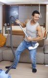 Homem novo que tem o divertimento em casa Fotografia de Stock