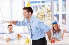Homem novo que tem o divertimento no partido de escritório imagem de stock royalty free