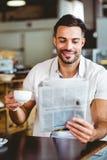 Homem novo que tem o jornal da leitura da xícara de café foto de stock