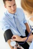 Homem novo que tem a pressão sanguínea tomada Fotografia de Stock Royalty Free