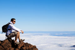 Homem novo que tem um resto em um pico alto sobre nuvens Fotos de Stock