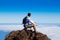 Homem novo que tem um resto em um pico alto sobre nuvens Fotos de Stock Royalty Free