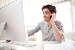 Homem novo que tem uma chamada na frente do computador Fotografia de Stock Royalty Free
