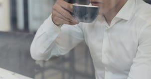 Homem novo que tem uma ruptura de café, bebe o café e a utilização de um portátil, fim da mão acima vídeos de arquivo