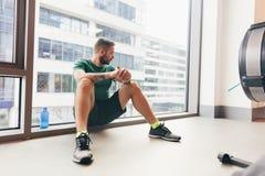 Homem novo que tem uma ruptura em seu exercício do gym fotos de stock royalty free