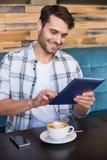 Homem novo que tem a xícara de café usando a tabuleta Imagens de Stock
