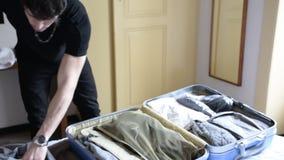 Homem novo que tenta fechar sua mala de viagem vídeos de arquivo