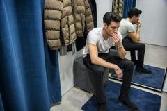 Homem novo que tenta na roupa na loja de roupa foto de stock royalty free