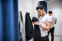Homem novo que tenta na roupa na loja de roupa fotos de stock
