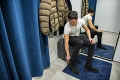 Homem novo que tenta na roupa na loja de roupa imagens de stock royalty free