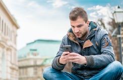 Homem novo que texting no telefone ao sentar-se Imagens de Stock