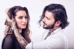 Homem novo que toca no cabelo de uma mulher sensual no fundo branco Imagens de Stock