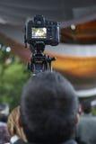 Homem novo que toma fotos com um tripé outdoors Fotografia de Stock Royalty Free